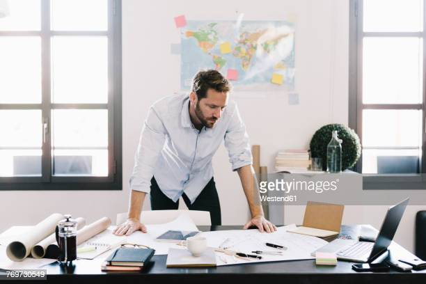 architect looking at construction plan in his office - bending over stock pictures, royalty-free photos & images