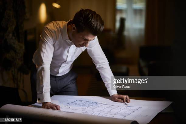 architect looking at floor plan on desk - architect stockfoto's en -beelden