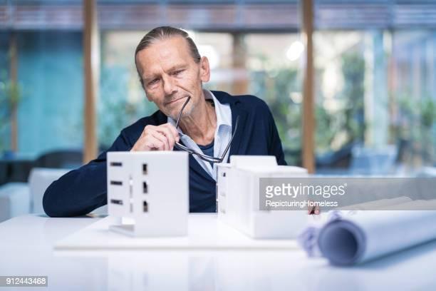 Architekt in Gedanken schaut auf ein Modell