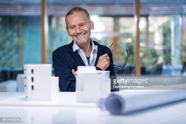 Architekt schaut lächelnd auf ein Modell