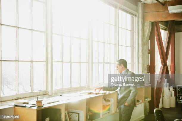 Architect looking at material samples while working on a project in office