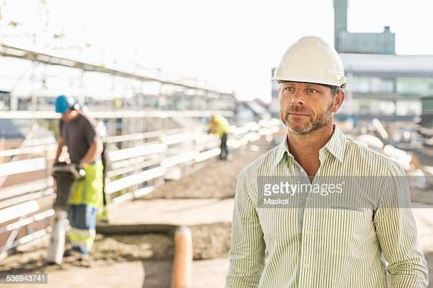 Architect looking away while standing at construction site