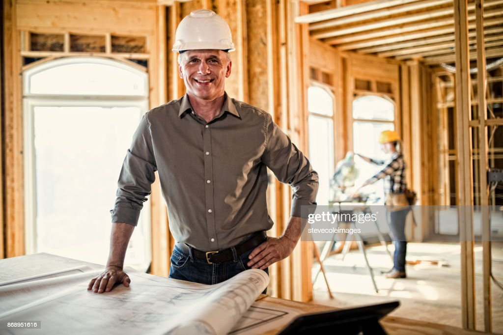 Architect looking over blueprints : Stock Photo