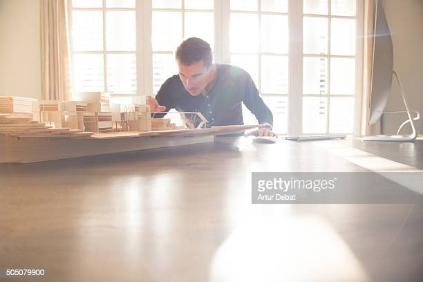 architect man working on desk office with bright morning light through the window at home. - architect stock pictures, royalty-free photos & images