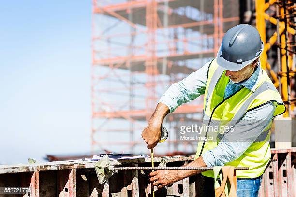 Architect measuring metal at site
