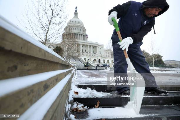 Architect of the Capitol Mason Perry Curtis shovels snow in front of the US Capitol January 4 2018 in Washington United States A large winter storm...