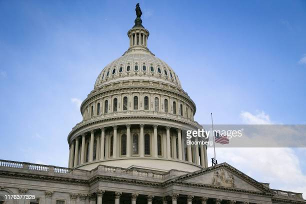 Architect of the Capitol workers lower an American flag to half mast at the U.S. Capitol following the death of Representative Elijah Cummings, a...