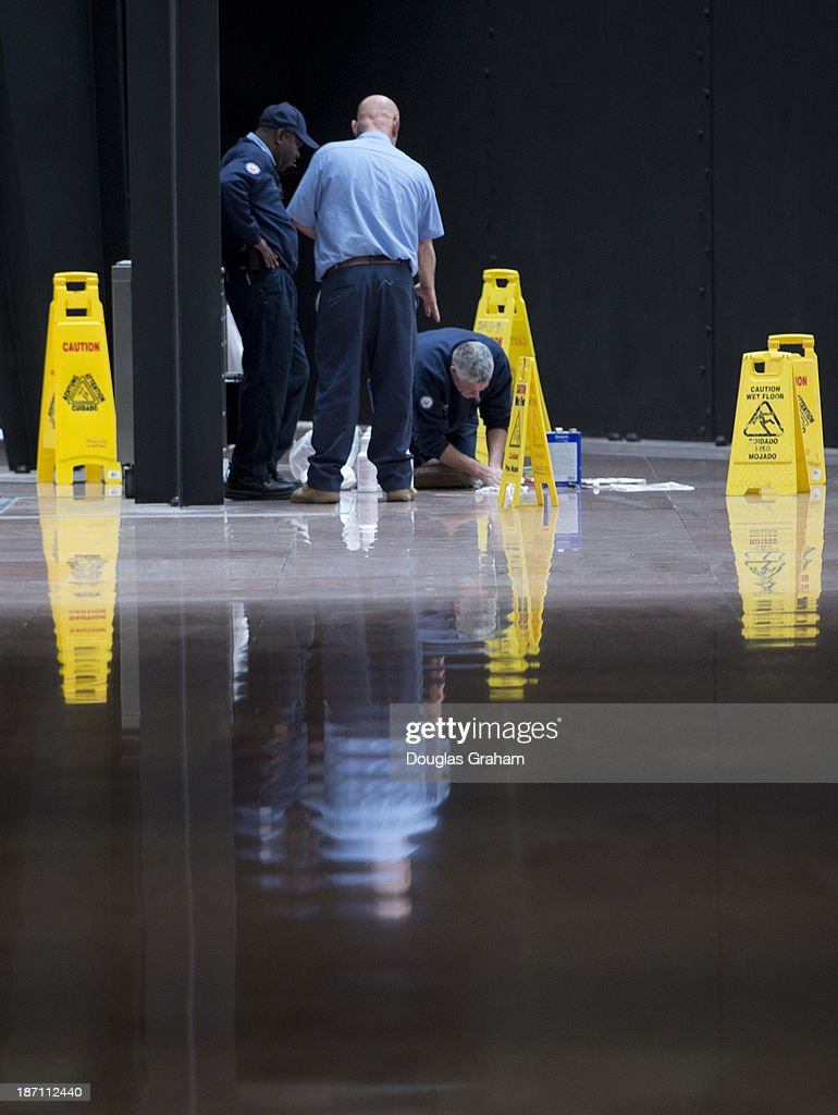 Architect of the Capitol workers make repairs to sections of the floor in the Hart Senate Office Building atrium in Washington, D.C. on November 6, 2013.