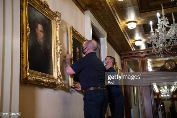 Architect of the Capitol workers remove the portrait of Confederate speaker James Orr from a wall in the Speaker's Lobby of the US Capitol on June 18...