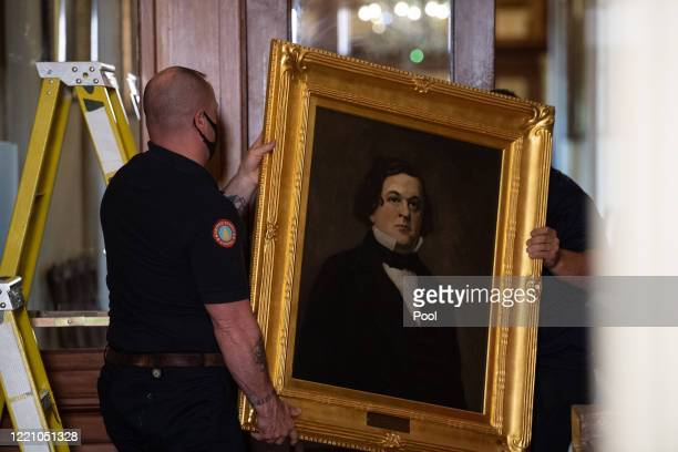 Architect of the Capitol workers remove the portrait of former House Speaker Howell Cobb of Georgia from a wall in the Speaker's Lobby of the US...