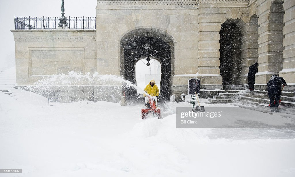 Architect of the Capitol workers struggle to keep up with the snow as they clear the area around the carriage entrance on the Senate side of the Capitol on Saturday, Dec. 19, 2009.