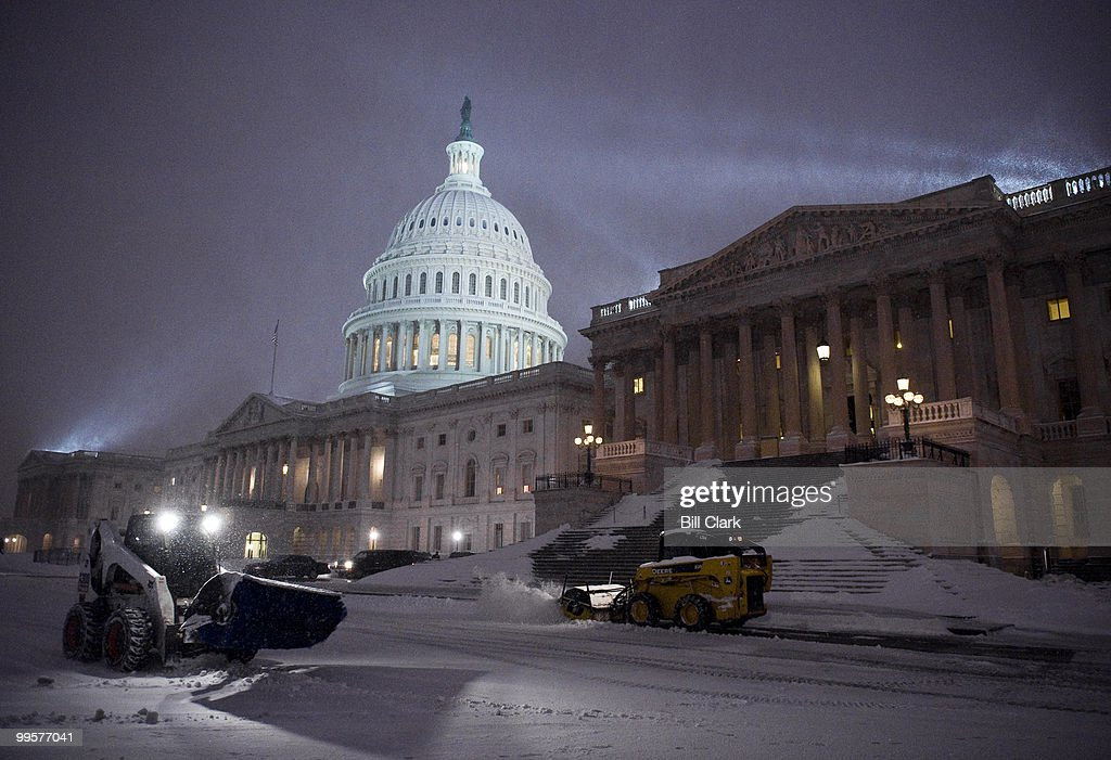 Architect of the Capitol workers struggle to keep up with the snow as they clear the East Plaza of the Capitol before sunrise on Saturday, Dec. 19, 2009.