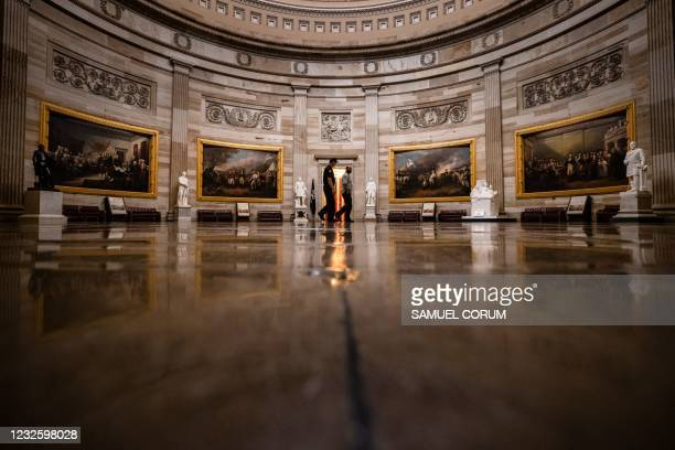 Architect of the Capitol workers walk through the Rotunda in the US Capitol building on Capitol Hill in Washington, DC on April 29, 2021.