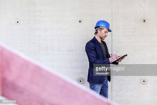 Architect on construction site writing