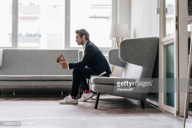 architect on couch holding architectural model - sitzen stock-fotos und bilder