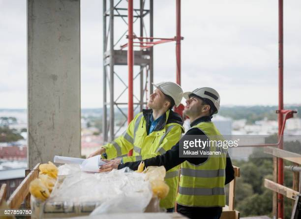 Architect on high rise construction site with blueprints