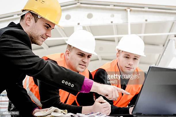 Architect pointing plans on laptop