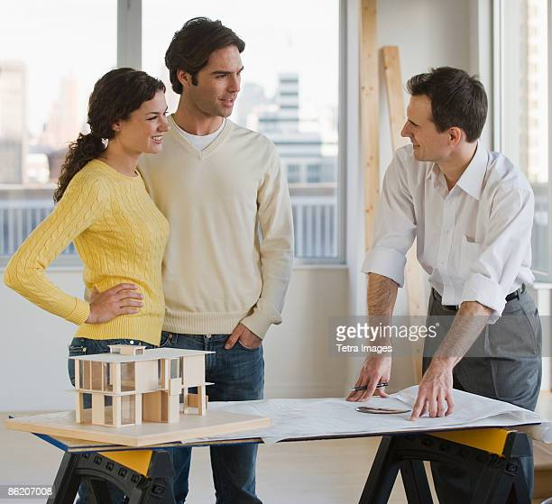 Architect presenting blueprints to couple