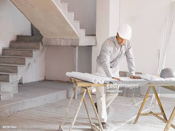 architect reviewing blueprints at construction site - real estate developer stock pictures, royalty-free photos & images