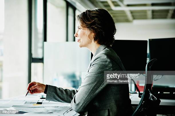 architect reviewing plans at office workstation - world at your fingertips stock pictures, royalty-free photos & images