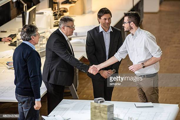 Architect shaking hand with client in office