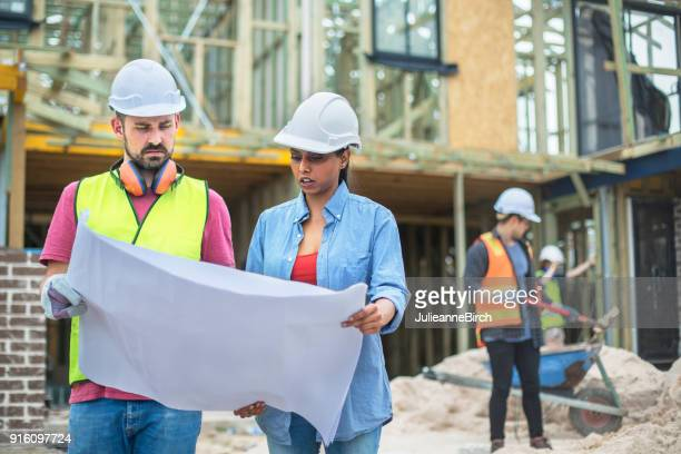 Architect showing plans to foreman on building site