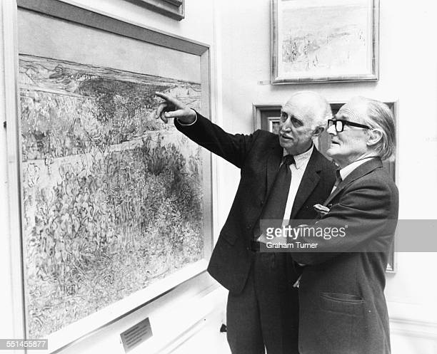 Architect Sir Hugh Casson , President of the Royal Academy, and artist Charles Wollaston inspecting the painting 'Les Causses' which won the Summer...