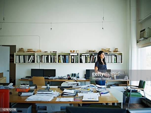 Architect standing in office looking out window