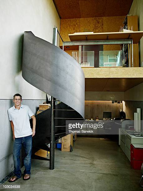 Architect standing in small office near staircase