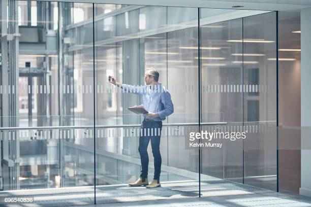 Architect taking photo with cell phone in modern office