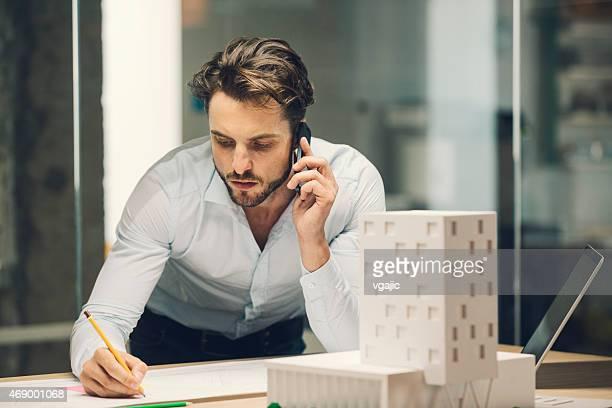 Architecte discutant sur le téléphone intelligent du bureau.