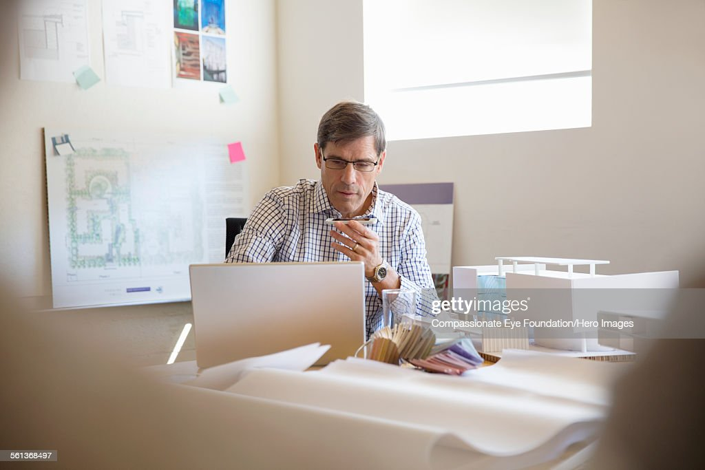 Architect using cell phone and laptop in office : Stock Photo