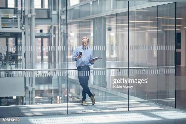 architect using cell phone in office hallway - equipment stock pictures, royalty-free photos & images