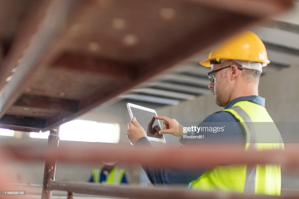 Architect using laptop at construction site : Stock Photo