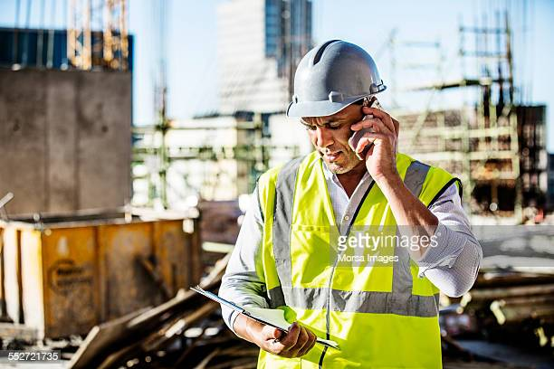 Architect using mobile phone at construction site