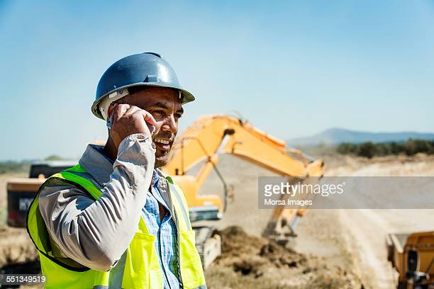 architect using mobile phone at quarry - baumaschine stock-fotos und bilder