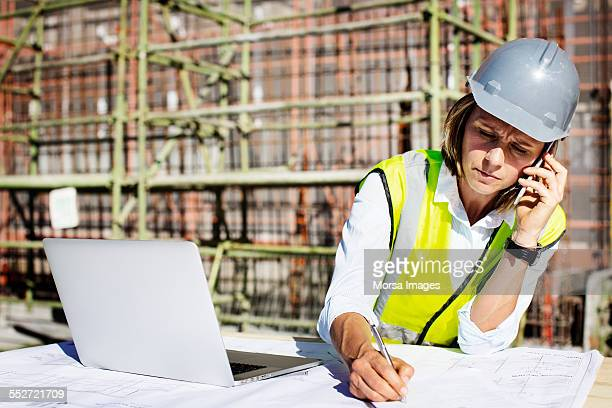 architect using mobile phone while working at site - bouwvakker stockfoto's en -beelden