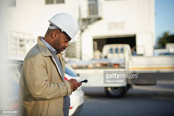 Architect using phone at construction site