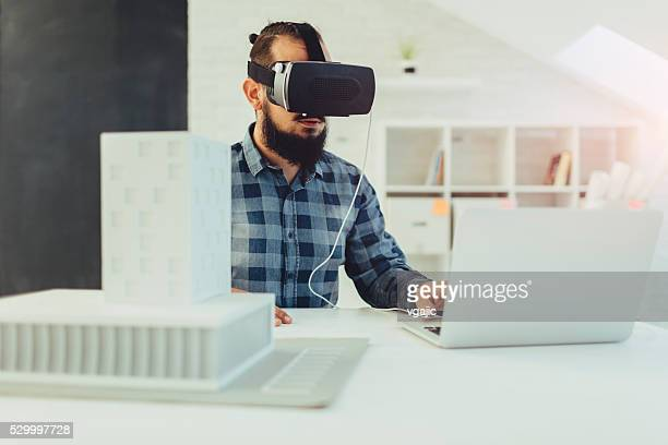 Architect using virtual reality glasses in his office.