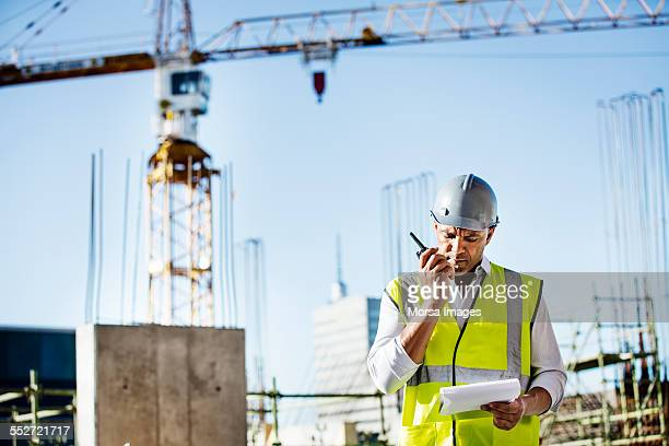Architect using walkie-talkie at construction site
