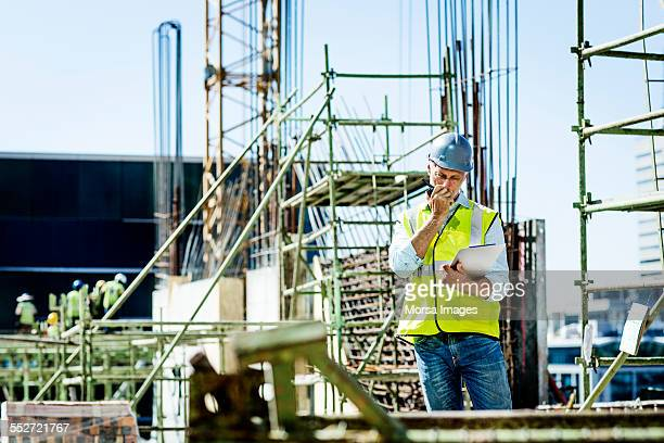 Architect using walkie-talkie at site