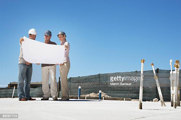 architect viewing blueprints with home owners - real estate developer stock pictures, royalty-free photos & images
