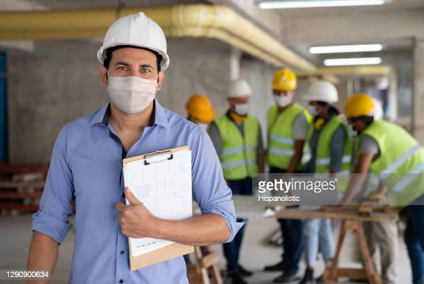 architect wearing a facemask while working at a construction site - biosecurity stock pictures, royalty-free photos & images