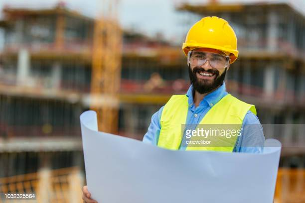 architect with blueprint looking at camera - mid adult stock pictures, royalty-free photos & images