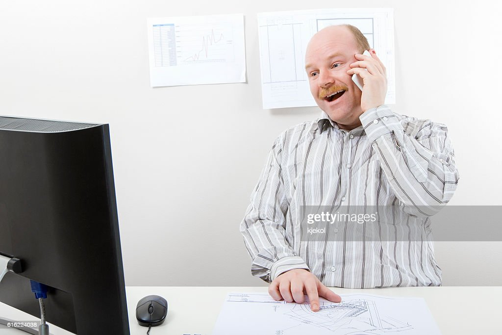Architect With Blueprint Using Mobile Phone At Desk : Stockfoto
