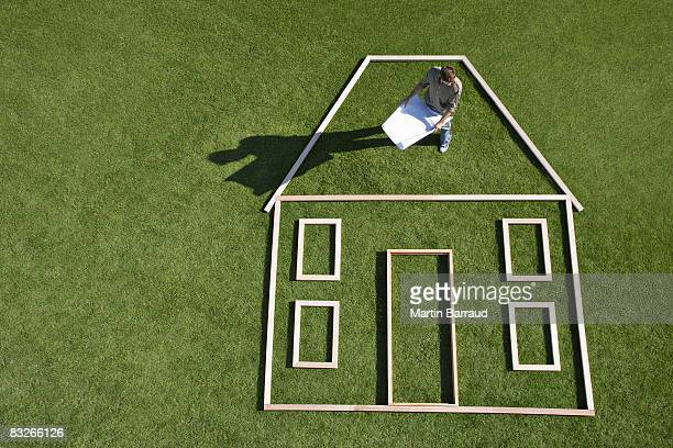 Architect with blueprints standing inside house outline