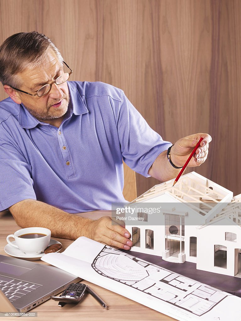Architect with model house on desk : Foto stock