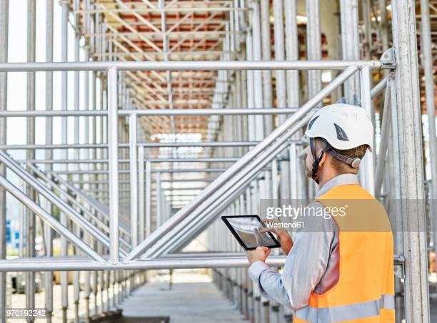 Architect with tablet wearing hard hat on construction site