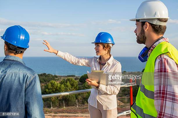 architect woman giving instructions on construction site - marine engineering stock photos and pictures