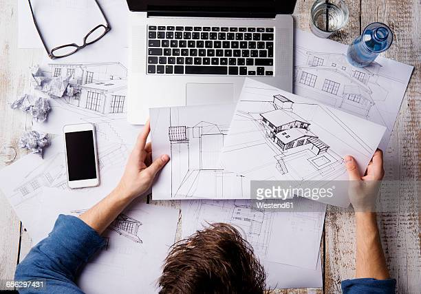 Architect working at desk with laptop, looking at sketches